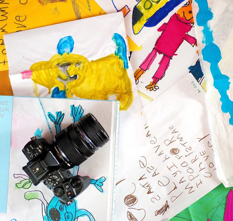 Photo of colourful children's drawings and paintings with camera. Jules is a professional photographer and uses her skills to craft memory books.