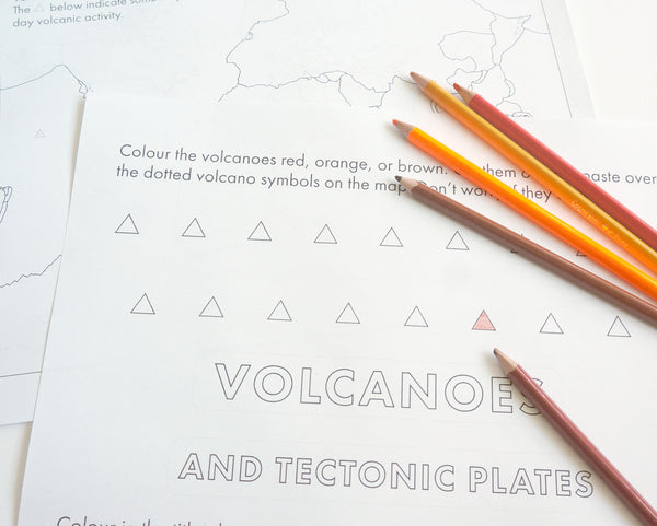 Page of a worksheet on volcanoes showing triangular cut and paste symbols with a handful of coloured pencils