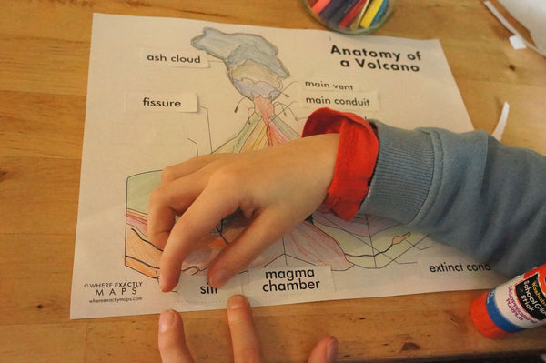 a boy placing labels on a volcano diagram worksheet