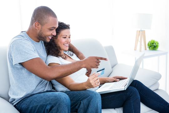 Man and women smiling while online shopping on a couch