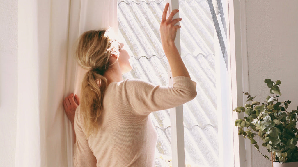 women standing looking out her window, enjoying the calm after her home is cleaned with Clean Crate Subscription Natural cleaning products
