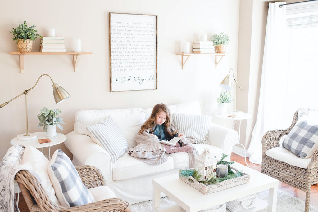 little girl relaxing reading in a beautiful white living room, cleaned and detoxified with Clean Crate products.
