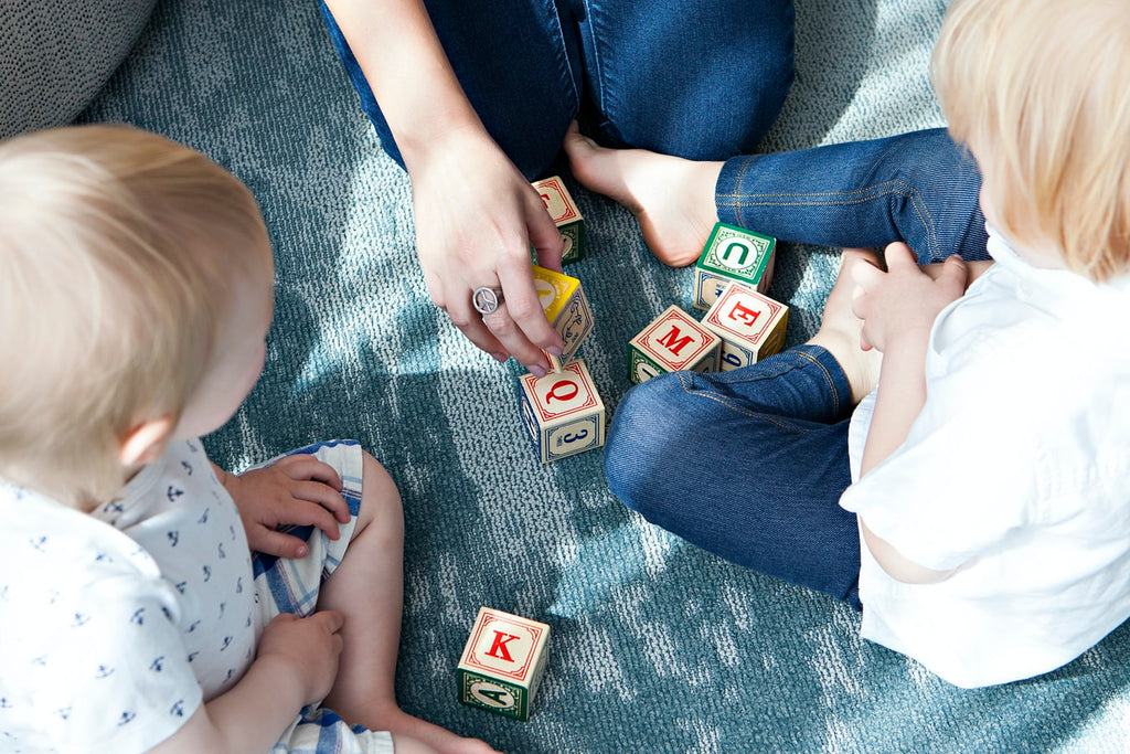 A mother plays game with two children on a clean carpet refreshed with Clean Crate product