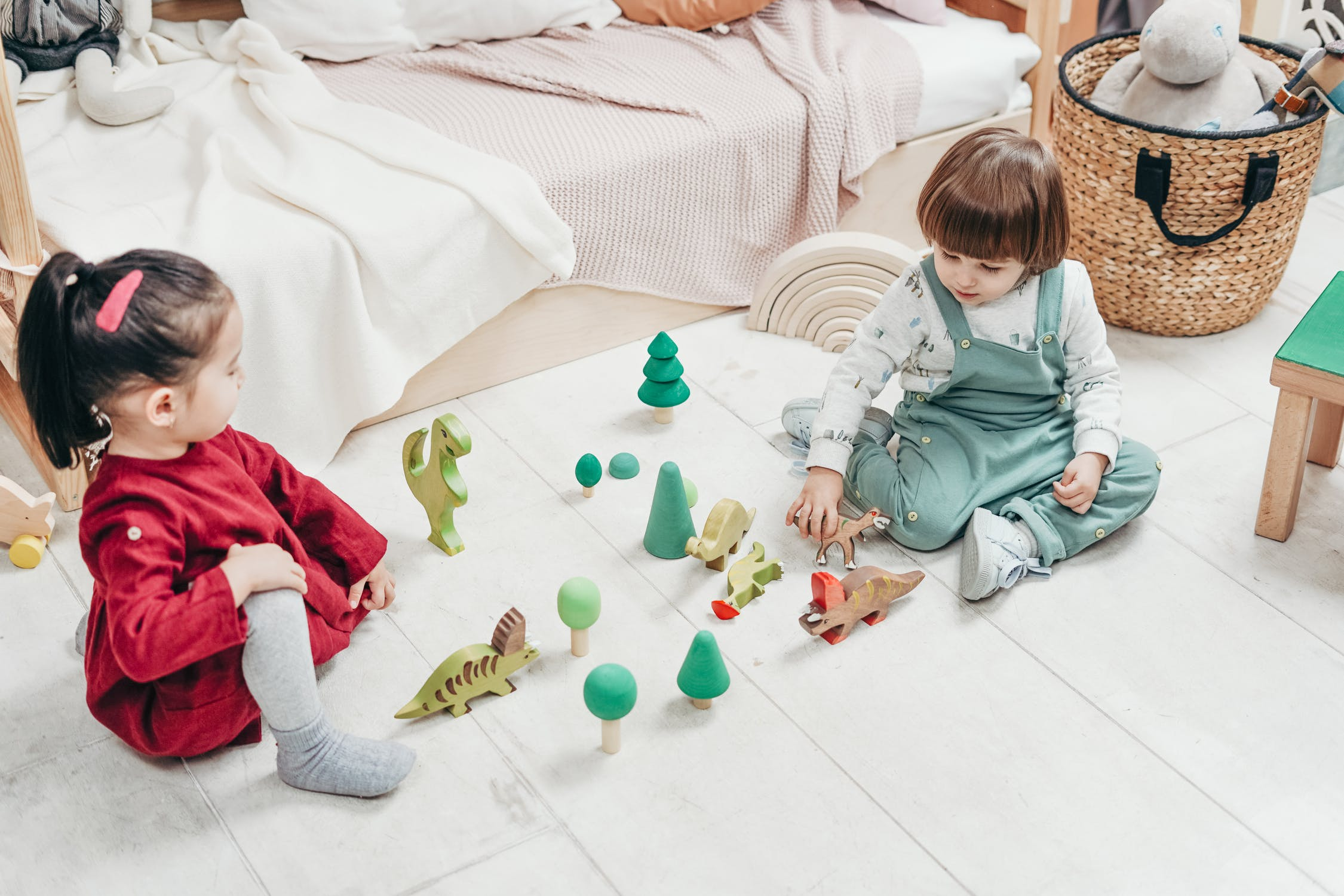 Two young children play with toys on the floor of a bedroom.
