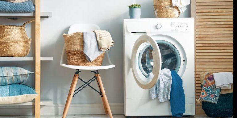 A laundry room with washing machine, clothing, and pillows.