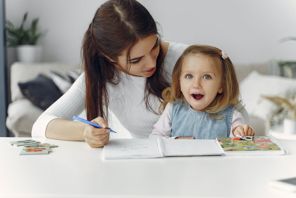 mother and daughter drawing together. Daughter excited. Learning about eco friendly environmentally aware living. Sparkling home cleaned with Clean Crate Subscription box of home cleaning products, all natural, eco friendly non-toxic, Canadian