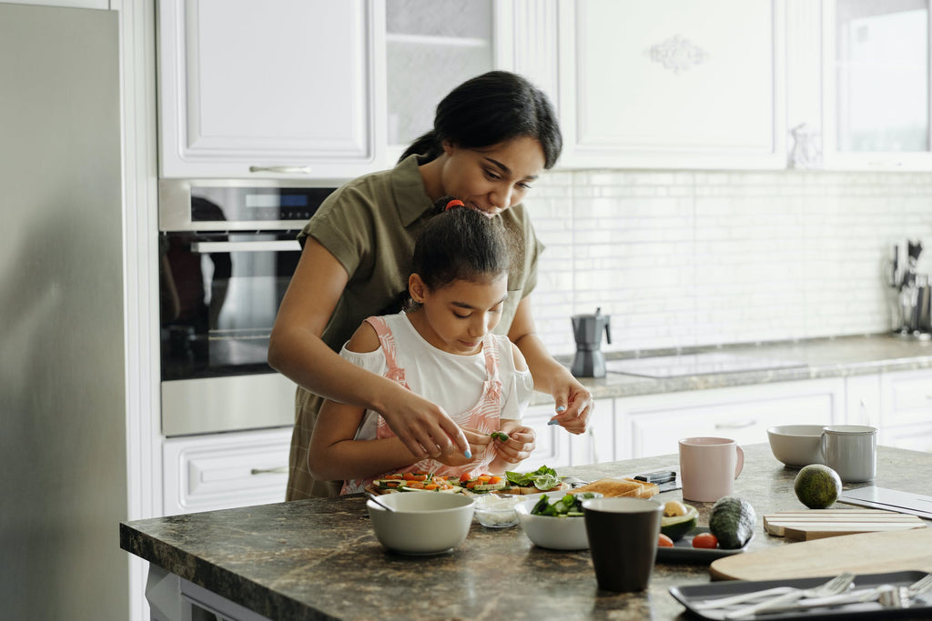 mom and daughter making a healthy meal together in a clean kitchen. Eco friendly family uses non toxic natural cleaning products from the Clean Crate Subscription Box.