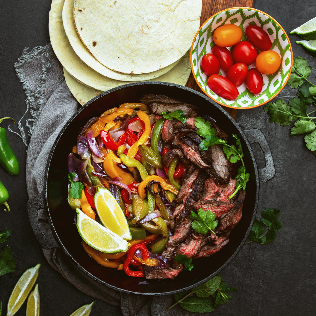 tequila marinated steak fajitas in a cooking pan with taco tortilla and tomatoes in a bowl