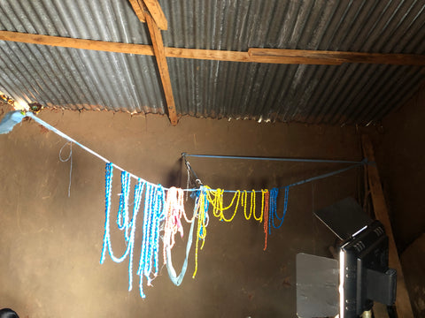 paper bead necklaces hanging on a line drying inside a mud hug on a line stretched across the hut