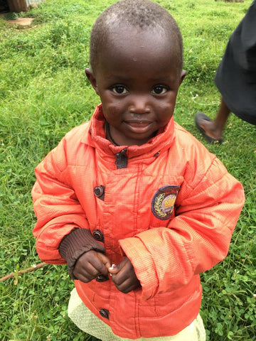 black child wearing peach colored jacket
