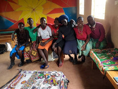group of women sitting on a wooden long bench in a building with blankets and products around on the floore.