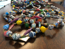 "Load image into Gallery viewer, Hand made colorful long length multicolor necklace made from magazines with accent seed beads in between each hand rolled paper bead. Stylish and Fashionable for casual or dressy. Fair trade.  Approximately 33"" L  Multicolor - each strand is slightly different depending on magazines used.  Includes a few solid colors as shown in photos."