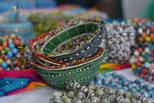 Fair trade hand crafted basket made from seed beads. Round shape bowl style. Stack of bowls in various colors