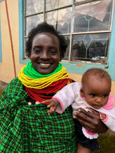 Load image into Gallery viewer, Patricia pictured in traditional Turkana dress with here youngest child Shari