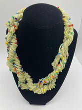 "Load image into Gallery viewer, Stand out in style with this beautiful hand made braided style beaded necklace.  Approximately 18"" end to end.   The Dorcas necklace is named after one of our ladies whose photo you will find within this collection. Off white with multi color bead accent"