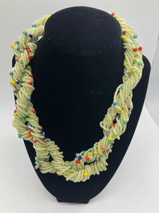 "Stand out in style with this beautiful hand made braided style beaded necklace.  Approximately 18"" end to end.   The Dorcas necklace is named after one of our ladies whose photo you will find within this collection. Off white with multi color bead accent"
