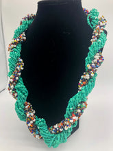 "Load image into Gallery viewer, Stand out in style with this beautiful hand made braided style beaded necklace.  Approximately 18"" end to end.   The Dorcas necklace is named after one of our ladies whose photo you will find within this collection. Aqua and white multi accent"