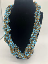 "Load image into Gallery viewer, Stand out in style with this beautiful hand made braided style beaded necklace.  Approximately 18"" end to end.   The Dorcas necklace is named after one of our ladies whose photo you will find within this collection. Light blue and gold"