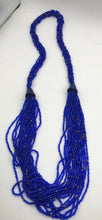 Load image into Gallery viewer, Make a statement with this beautiful handmade seed bead necklace.  Styled with braided beads around the neck flowing into a loose styled design.  Royal blue with gold bead accent
