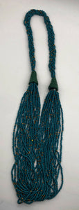 Make a statement with this beautiful handmade seed bead necklace.  Styled with braided beads around the neck flowing into a loose styled design. Teal with gold bead accent