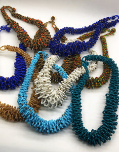 "Stand out in style with this beautiful handmade loop bead style necklace.  Hover over the photo to see the detail of how the beads are made into a loop design.  Thoughtfully designed for style and stand out fashion. Approximately 18"" end to end.  Multiple colors shown."