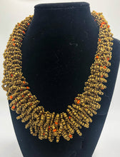 "Load image into Gallery viewer, Stand out in style with this beautiful handmade loop bead style necklace.  Hover over the photo to see the detail of how the beads are made into a loop design.  Thoughtfully designed for style and stand out fashion. Approximately 18"" end to end.  Gold with orange accent beads"