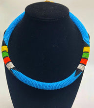 Load image into Gallery viewer, Wear the epitome of Kenya style with The Bintiah necklace.  This necklace is handmade using colorful seed beads that are intricately and tightly wrapped around a solid piece fo make a stunning statement with any outfit.  Multiple colors pictured. Light blue with colorful bead accend.