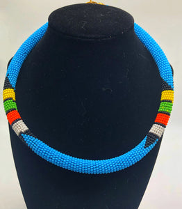 Wear the epitome of Kenya style with The Bintiah necklace.  This necklace is handmade using colorful seed beads that are intricately and tightly wrapped around a solid piece fo make a stunning statement with any outfit.  Multiple colors pictured. Light blue with colorful bead accend.