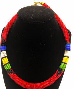 Wear the epitome of Kenya style with The Bintiah necklace.  This necklace is handmade using colorful seed beads that are intricately and tightly wrapped around a solid piece fo make a stunning statement with any outfit.  Red pictured with colorful accent