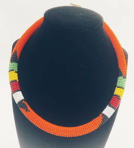 Wear the epitome of Kenya style with The Bintiah necklace.  This necklace is handmade using colorful seed beads that are intricately and tightly wrapped around a solid piece fo make a stunning statement with any outfit.  Orange with colorful bead accent