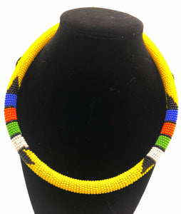 Wear the epitome of Kenya style with The Bintiah necklace.  This necklace is handmade using colorful seed beads that are intricately and tightly wrapped around a solid piece fo make a stunning statement with any outfit.  Yellow  with colorful bead accent