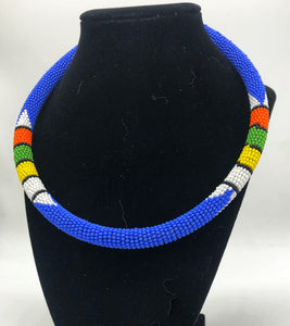 Wear the epitome of Kenya style with The Bintiah necklace.  This necklace is handmade using colorful seed beads that are intricately and tightly wrapped around a solid piece fo make a stunning statement with any outfit.   blue with colorful bead accent