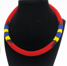 Load image into Gallery viewer, Wear the epitome of Kenya style with The Bintiah necklace.  This necklace is handmade using colorful seed beads that are intricately and tightly wrapped around a solid piece fo make a stunning statement with any outfit.  Red with blue, yellow and black accent beads