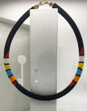 Load image into Gallery viewer, Wear the epitome of Kenya style with The Bintiah necklace.  This necklace is handmade using colorful seed beads that are intricately and tightly wrapped around a solid piece fo make a stunning statement with any outfit.   Black with colorful bead accent.