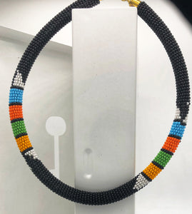 Wear the epitome of Kenya style with The Bintiah necklace.  This necklace is handmade using colorful seed beads that are intricately and tightly wrapped around a solid piece fo make a stunning statement with any outfit.   Black with colorful bead accent.
