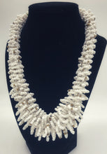 "Load image into Gallery viewer, Stand out in style with this beautiful handmade loop bead style necklace.  Hover over the photo to see the detail of how the beads are made into a loop design.  Thoughtfully designed for style and stand out fashion. Approximately 18"" end to end. white with gold accent beads"