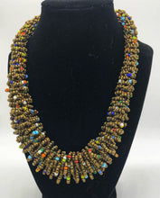 "Load image into Gallery viewer, Stand out in style with this beautiful handmade loop bead style necklace.  Hover over the photo to see the detail of how the beads are made into a loop design.  Thoughtfully designed for style and stand out fashion. Approximately 18"" end to end.  Gold with multi color accent beads"