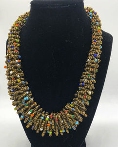 "Stand out in style with this beautiful handmade loop bead style necklace.  Hover over the photo to see the detail of how the beads are made into a loop design.  Thoughtfully designed for style and stand out fashion. Approximately 18"" end to end.  Gold with multi color accent beads"