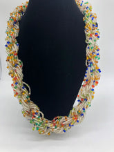 "Load image into Gallery viewer, Stand out in style with this beautiful hand made braided style beaded necklace.  Approximately 18"" end to end.   The Dorcas necklace is named after one of our ladies whose photo you will find within this collection. clear white with multi color accent"
