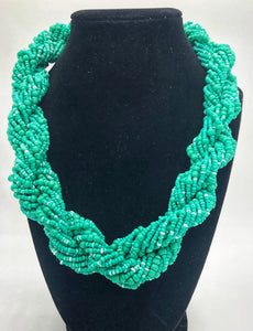 "Stand out in style with this beautiful hand made braided style beaded necklace.  Approximately 18"" end to end.   The Dorcas necklace is named after one of our ladies whose photo you will find within this collection. Aqua"