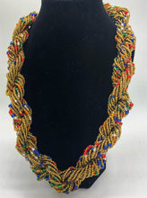 "Load image into Gallery viewer, Stand out in style with this beautiful hand made braided style beaded necklace.  Approximately 18"" end to end.   The Dorcas necklace is named after one of our ladies whose photo you will find within this collection. Gold with multi color accent"