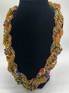 "Stand out in style with this beautiful hand made braided style beaded necklace.  Approximately 18"" end to end.   The Dorcas necklace is named after one of our ladies whose photo you will find within this collection. Gold with multi color accent"