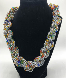 "Stand out in style with this beautiful hand made braided style beaded necklace.  Approximately 18"" end to end.   The Dorcas necklace is named after one of our ladies whose photo you will find within this collection. Silver with multicolor accent"