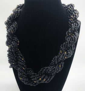 "Stand out in style with this beautiful hand made braided style beaded necklace.  Approximately 18"" end to end.   The Dorcas necklace is named after one of our ladies whose photo you will find within this collection. black with gold bead accent"
