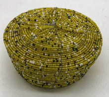 Load image into Gallery viewer, Fair Trade hand crafted basket made from seed beads. Round shape with lid. These baskets take 1 full day to create.  yellow gold, black and white accent beads.