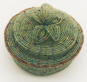 Fair Trade hand crafted basket made from seed beads. Round shape with lid. These baskets take 1 full day to create.  Pale green with gold accent around edge