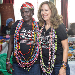 2 women standing and wearing strands of long paper beads in multiple colors also wearing baskets and beads t-shirts