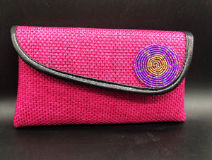 hot pink clutch with round beads around edge and black piping around edge of flap