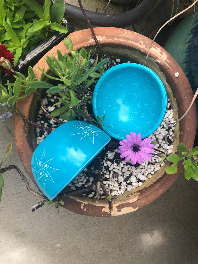Turquoise color soap stone bowl with small stars on the inside and larger ones carved into the outside.  Smooth surface.