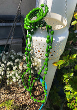 "Load image into Gallery viewer, Long handmade paper bead necklace and memory wrap bracelet set green color. Necklace is approximately 30"" long and usually worn doubled. Bracelet is a wrap bracelet. Handcrafted from magazines. Fair trade.   Color: Green memory wrap bracelet and necklace pictured."